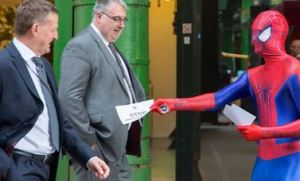 Spiderman hands out leaflets